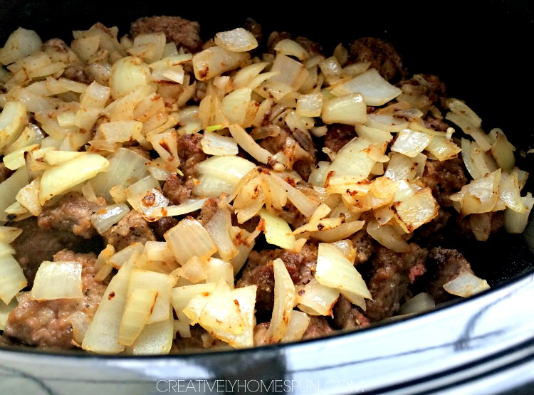 Browned onions on top of stew meat in crock pot